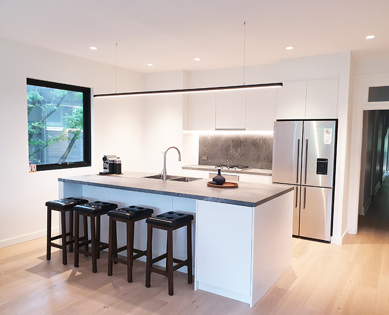37. Small white kitchen with stone benchtop island with breakfast bar