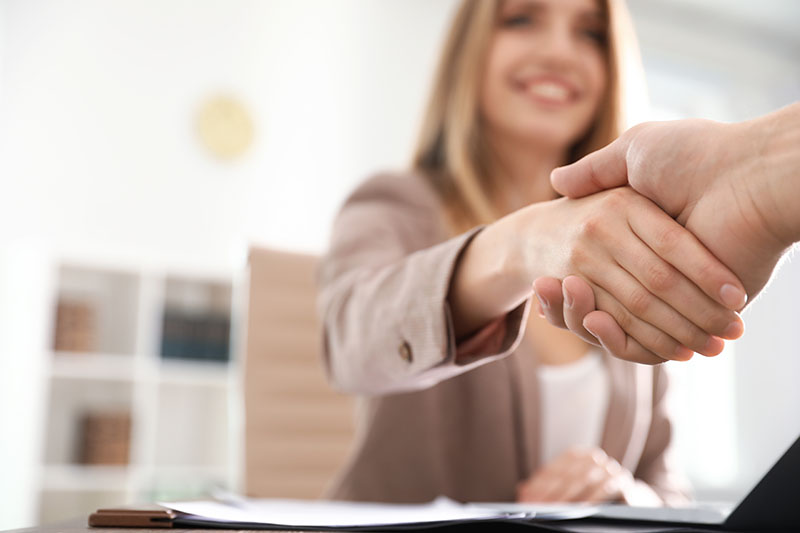 Business partners shaking hands at table after meeting, closeup. Space for text